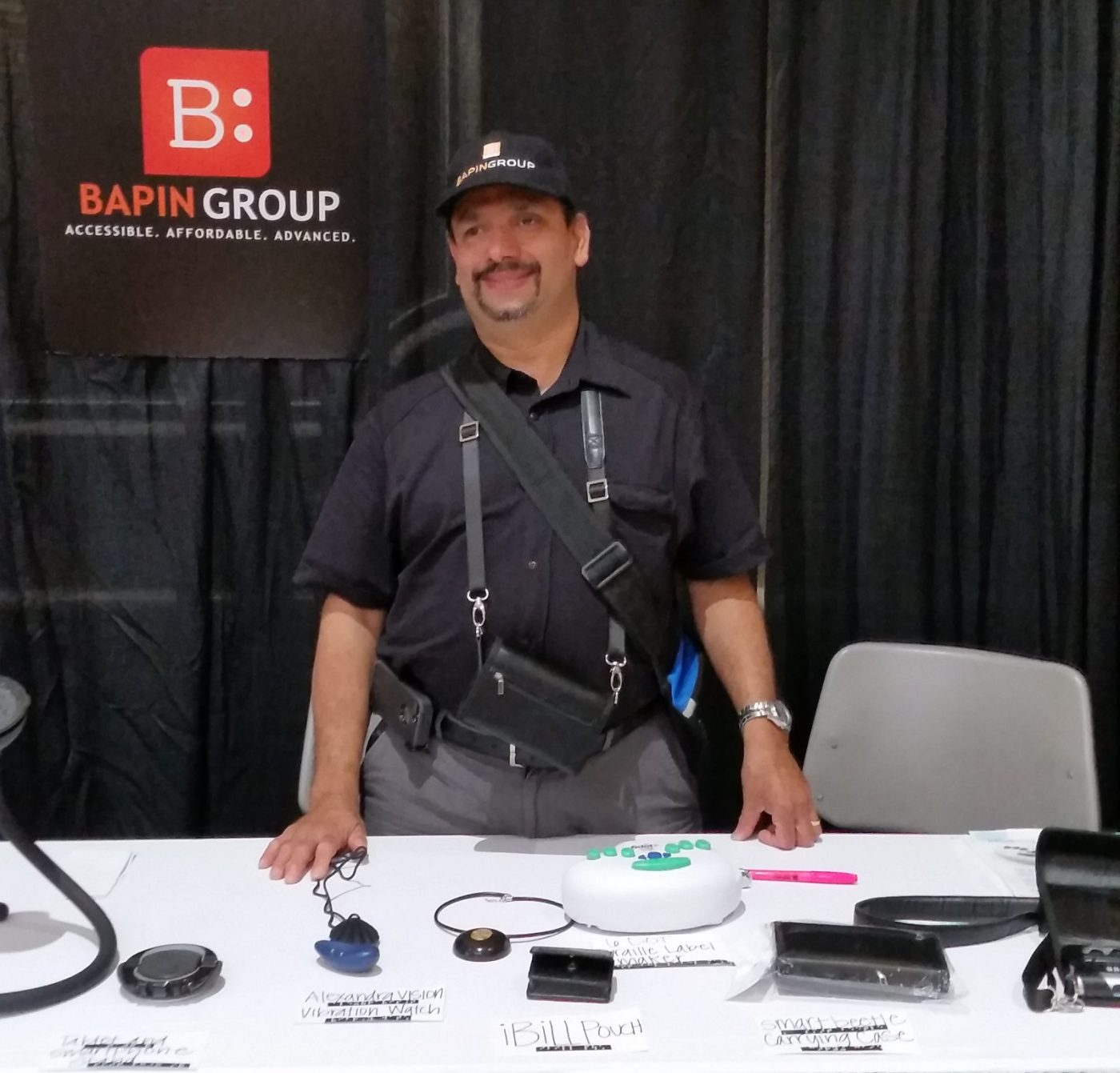 """Anindya Bhattacharyya, Bapin, wears a black shirt and hat and stands in front of a black backdrop. A sign reading """"Bapin Group. Accessible. Affordable. Advanced."""" appears above his left shoulder. In front of Bapin is a white table displaying a number of assistive technology devices."""