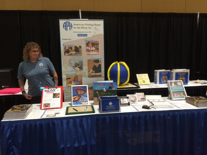 Karen A. Isham, a pale skinned woman with sandy, curly hair stands behind the APH display table, wearing glasses and a pale blue polo. Her arms are covered with tattoos.