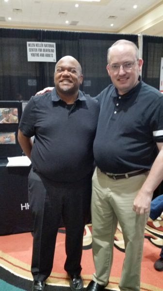A sign in the backgrounds reads: Helen Keller National Center for DeafBlind Youth and Adults. Cory Parker stands beside another man. The two men have their arms around each other's shoulders. Cory is shorter and has dark skin, a black polo shirt, black slacks, and shined black shoes. The taller man has fair skin, greying hair, and glasses. He wears a black polo shirt, tan slacks, and black shoes.