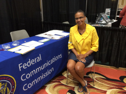 """Jackie Ellington, a female lawyer with dark skin and glasses, is wearing a bright yellow suit jacket and a grey skirt. She sits in front of a table with a blue cloth that says """"Federal Communications Commission."""""""