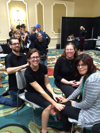 Three women, all brunettes, sit in a circle with smiles on their faces. Two of them, Hayley and Christina, sit with their knees touching and their hands on each other's knees, their left hands overlapping. A dark haired man, Hayley's SSP, who has a beard, kneels, also smiling, behind Hayley with his hands on her back.