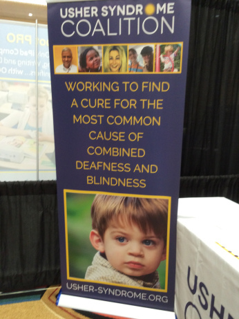 """A blue sign with photos of children printed on it, with the text """"Working to find a cure for the most common cause of combined deafness and blindness."""