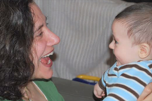 image of woman smiling and talking to smiling baby